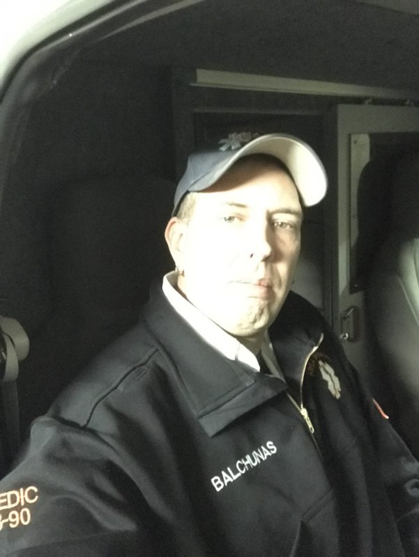 Brian sitting in an emergency vehicle taking a serious selfie.