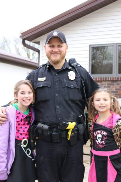 Timothy in police uniform with his two little girls