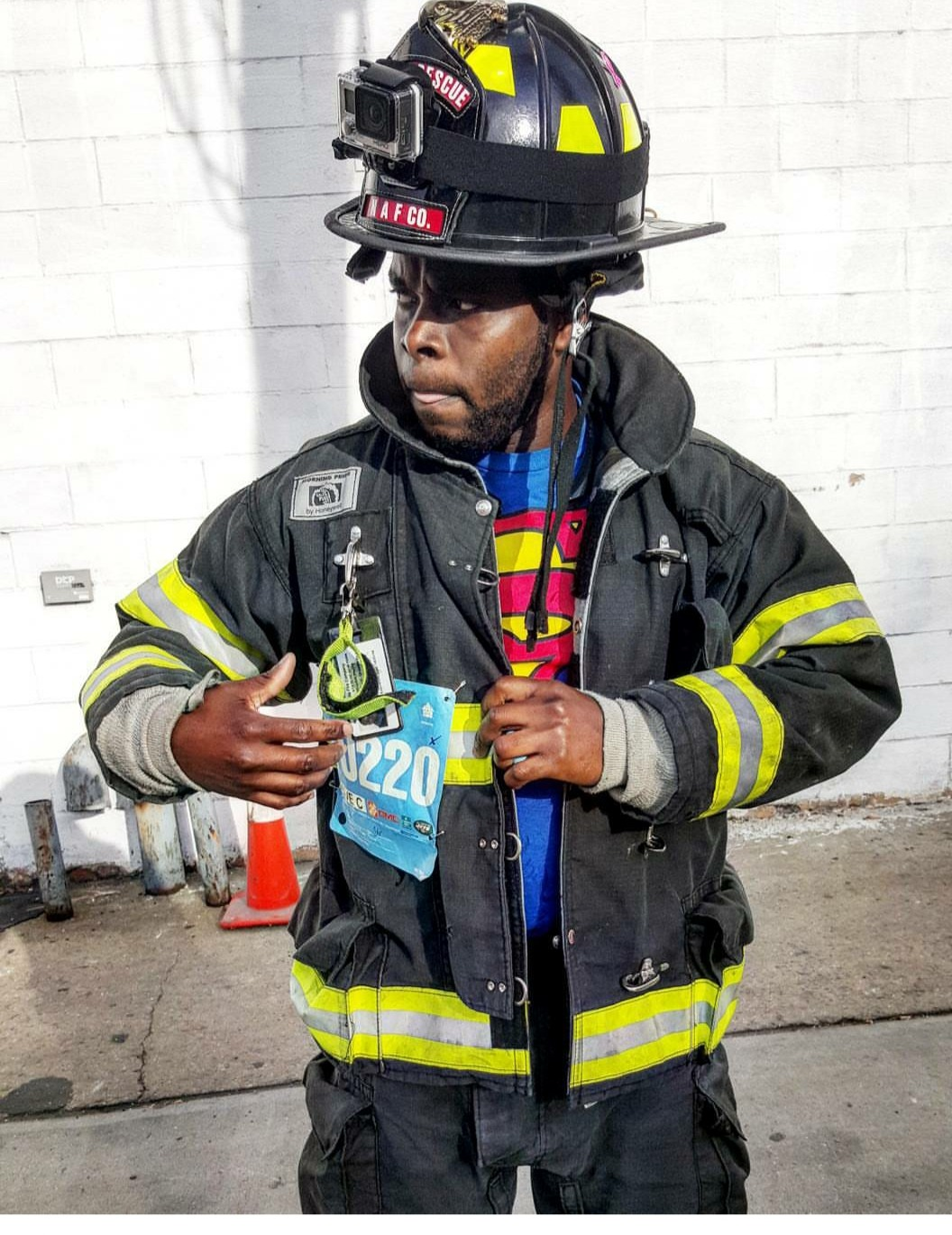 Rhodell in his firefighter uniform revealing a Superman shirt underneath.